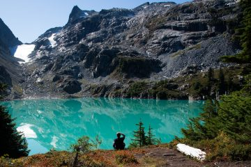 Man sat by glacier lake