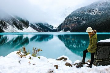 Woman wearing an insulated jacket by a lake