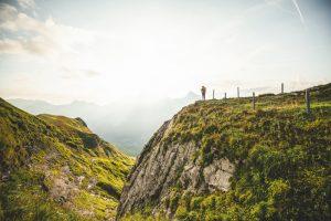 Via Alpina, 9. Etappe, Engstlenalp-Meiringen: Jana steht am Abgrund, blickt gegen die Sonne und das Panorama der Berner Alpen