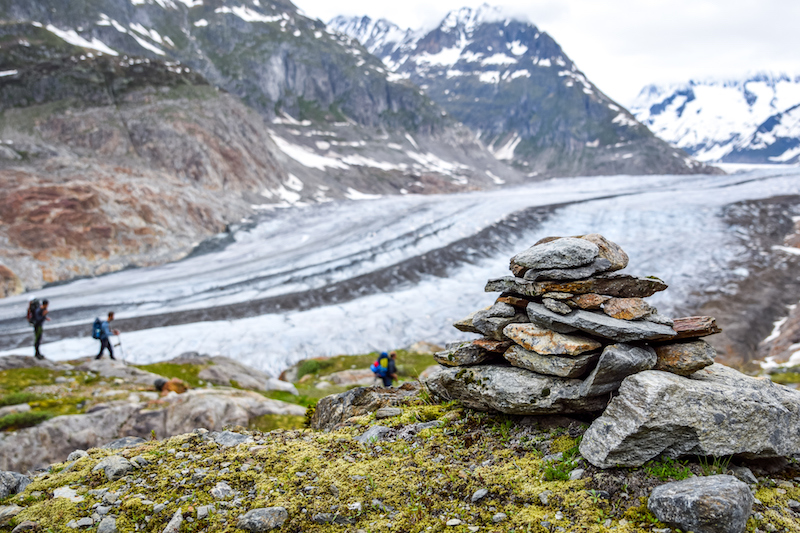 Stunning view of Aletsch glacier, the largest glacier in the European Alps, located in the Bernese Alps in Switzerland. A Stoneman (rock cairn) in the foreground. Unrecognizable hikers in background.