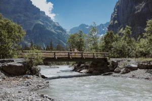 Hikers crossing a bridge in the Gastern Valley