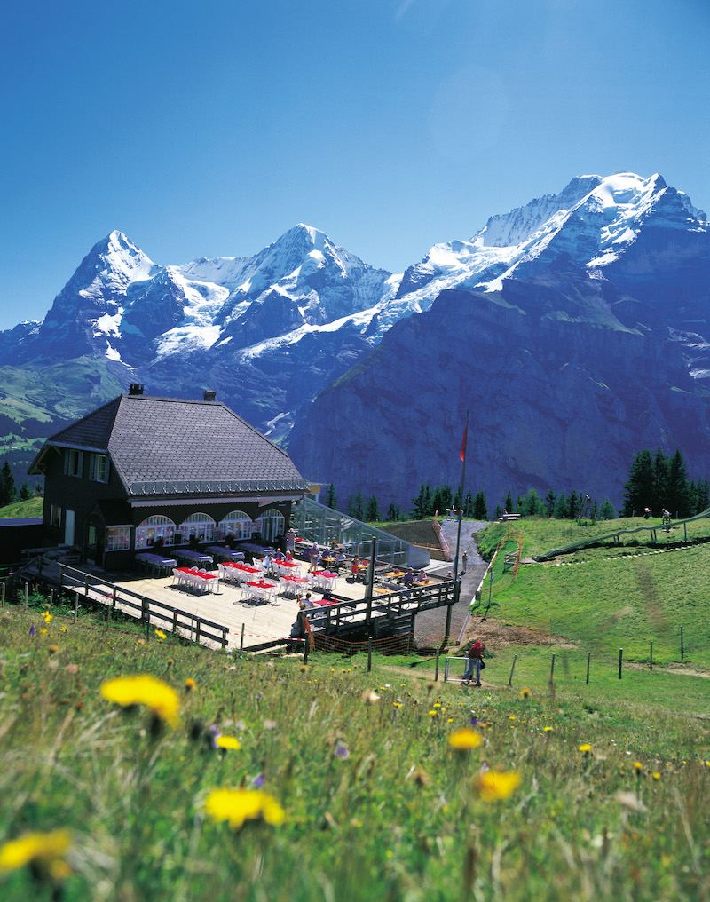 Switzerland Mountain restaurant Allmendhubel (1907 m) above Muerren in the Bernese Oberland. The majestic peaks of Eiger, Moench and Jungfrau loom in the back.