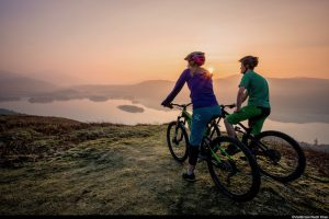 Two people on mountain bikes resting at the top of a fell above Derwentwater in Borrowdale, viewing the landscape at sunset.