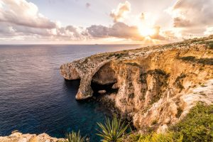 """Sunset over the """"Blue Grotto"""". A famous arch rock formation on the island country of Malta. Located in the Mediterranean Sea, Europe."""