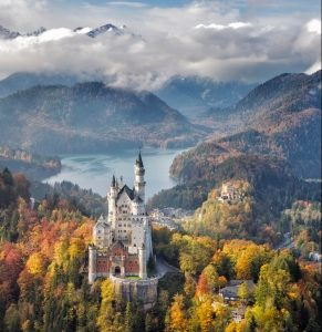 view of Neuschwanstein Castle on october 17th near Hohenschwangau, Germany during autumn afternoon surrounded by fall colours