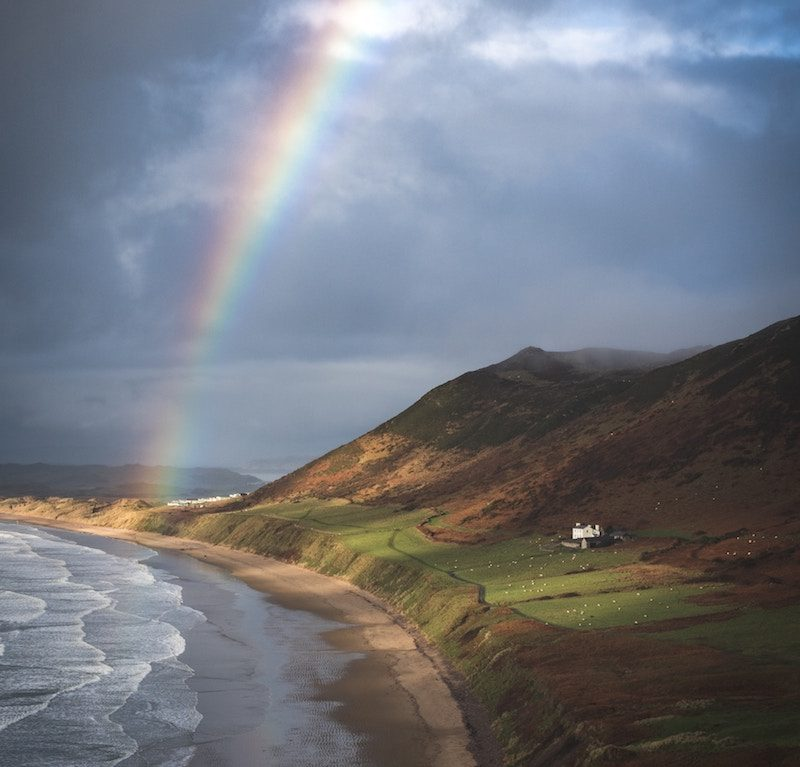 A rainbow over rhossili bay on the gower coast path